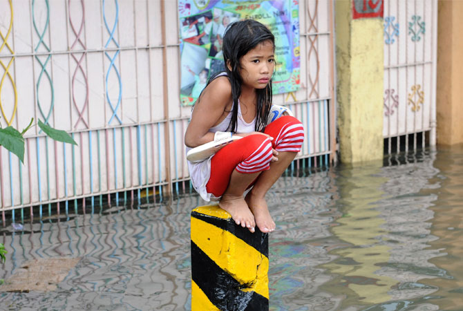A soaking wet child sits on a post on a flooded street in suburban Manila. More than one million people in and around the Philippine capital battled deadly floods on August 8 amid relentless monsoon rains, with neck-deep waters trapping slum dwellers and the wealthy on roofs. ? Photo by AFP