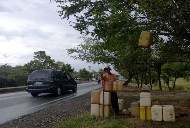 A ?pinpinero? man selling smuggled gasoline, waits for clients near a highway in Cucuta, Colombia, on its border with Venezuela. According to the latest report from UK website, a liter of gasoline in Venezuela costs about eight pennies.