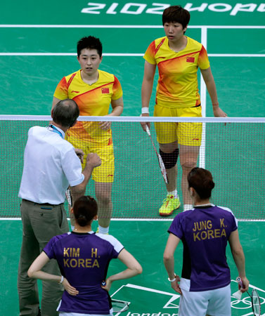 An unidentified official talks to world doubles champions Yu Yang, left, and Wang Xiaoli, as South Korea's Jung Kyung-eun, right, and Kim Ha-na, listen during their women's doubles badminton match at the 2012 Summer Olympics, Tuesday, July 31, 2012, in London. Wang and Yu and their South Korean opponents were booed loudly at the Olympics on Tuesday for appearing to try and lose their group match in Wembley Arena to earn an easier draw. ? Photo by AP