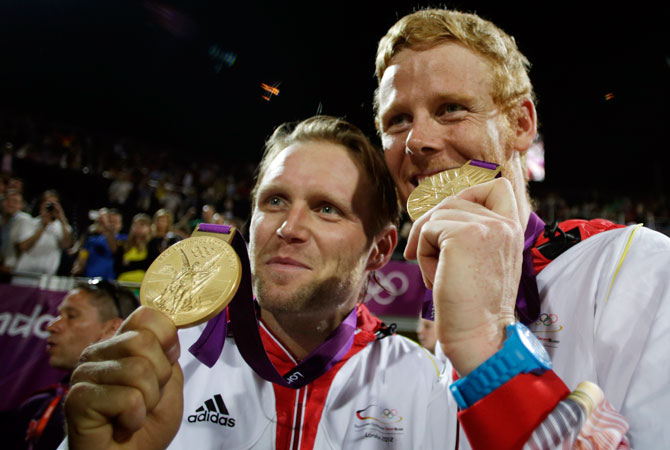 Germany's Julius Brink, left, and Jonas Reckermann celebrate with their gold medals after beating Brazil in the men's gold medal beach volleyball match at the 2012 Summer Olympics, Thursday, Aug. 9, 2012, in London.