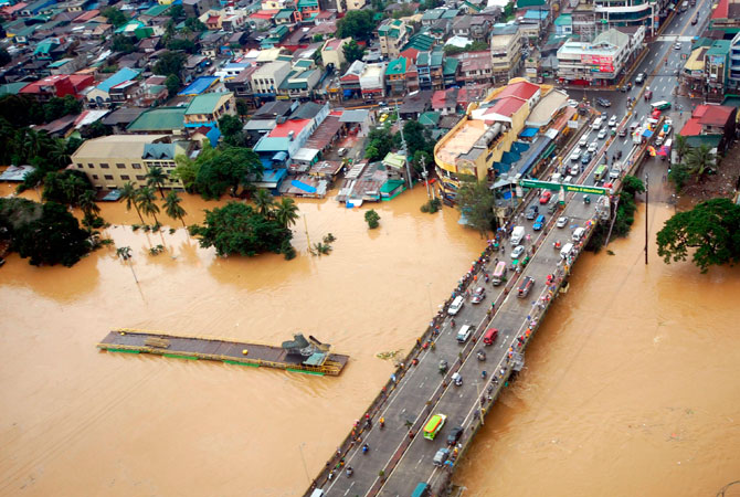 The overflowing Marikina river in Marikina, Metro Manila, is seen in this aerial photograph released by the Department of National Defense August 8, 2012. Emergency workers and troops rushed food, water and clothes to nearly 850,000 people displaced and marooned from deadly floods spawned by 11 straight days of southwest monsoon rains that soaked the Philippine capital and nearby provinces. ? Photo by Reuters