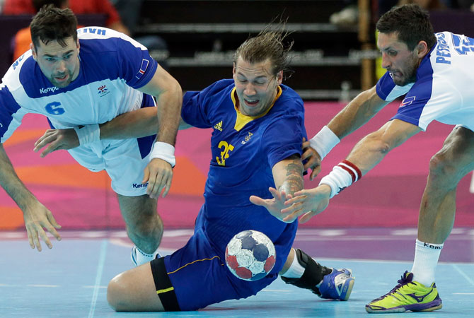 Andreas Nilsson of Sweden, center, Alexander Petersson (15) and Asgeir Hallgrimsson (6) of Iceland challenge during their men's handball preliminary match at the 2012 Summer Olympics, Thursday, Aug. 2, 2012, in London. ? Photo by AP