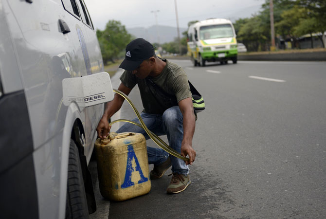 A man extracts gasoline from a Venezuelan car in Cucuta, Colombia, at the border with Venezuela. The government is pushing ahead with the unpopular measure in an attempt to end a business that experts say is more profitable than drug-trafficking