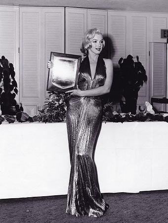 "In this March 1953 publicity photo provided by Running Press, Marilyn Monroe receives an award from Photoplay magazine at the Beverly Hills Hotel, in Beverly Hills, Calif. She is named ""Fastest Rising Star of 1952,"" and her choice of attire overshadows the event. The entire gown was made from ""one complete circle of fabric."" — AP Photo"