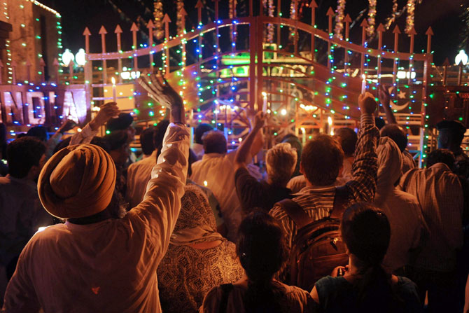 Pakistani and Indian revellers hold up candles and Indo-Pak joint national flags near the border gate during a vigil marking their respective countries' Independence Days at the India-Pakistan border in Wagah late on August 14, 2012. Pakistan celebrated Independence Day on August 14 and India on the 15th.  Photo by: AFP