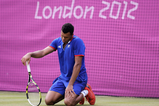 Jo-Wilfried Tsonga of France kneels on the court after missing a return against Milos Raonic of Canada at the All England Lawn Tennis Club at Wimbledon, in London, at the 2012 Summer Olympics, Tuesday, July 31, 2012. Tsonga won the match 6-3, 3-6, 25-23. The third set was the longest set in Olympic history. ? Photo by AP