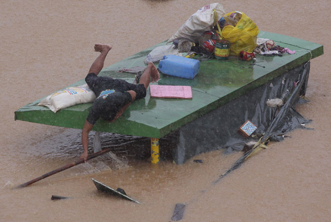 A man retrieves a wooden stick as he stays on top of waiting shed at a flooded area in Marikina, east of Manila, Philippines. A fresh deluge forced more evacuations along fast-rising rivers in the Philippine capital Thursday, as the city and surrounding areas struggled to deal with widespread flooding triggered by nearly two weeks of relentless rains. ? Photo by AP