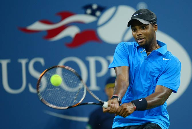 Donald Young returns a point to Roger Federer.