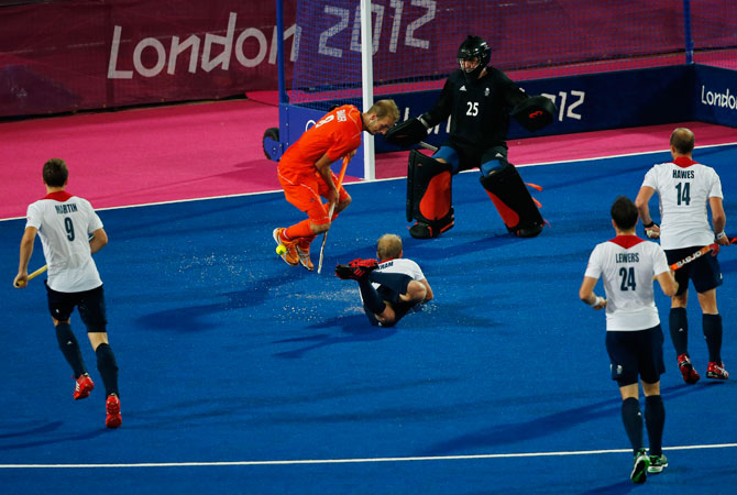 The Netherlands Billy Baker tries to shoot a goal as Britain's goal keeper James Fair, and Glenn Kirkham attempts to defend during a men's field hockey semifinal match at the 2012 Summer Olympics, Thursday, Aug. 9, 2012, in London.