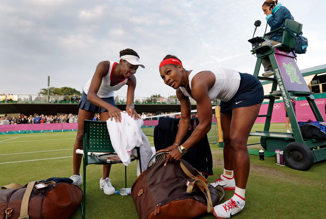 Venus, left, and Serena Williams of the United States pack up their gear after defeating Angelique Kerber and Sabine Lisicki of Germany in women's doubles at the All England Lawn Tennis Club in Wimbledon, London at the 2012 Summer Olympics, Tuesday, July 31, 2012. ? Photo by AP