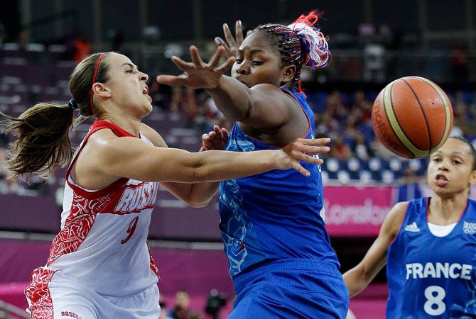Russia's Becky Hammon, left, passes around  France's Isabelle Yacoubou, center, during a semifinal women's basketball game at the 2012 Summer Olympics, Thursday, Aug. 9, 2012, in London.