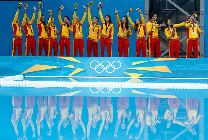 Members of the Spanish water polo team wave to the crowd with their silver medals on the podium during a medal ceremony for women's water polo after they were defeated by the United States in their women's water polo gold medal match at the 2012 Summer Olympics, Thursday, Aug. 9, 2012, in London.