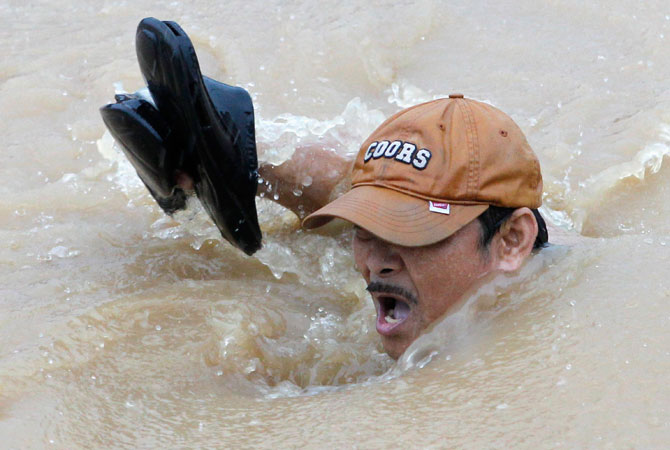 A man holds his shoes as he swims in floodwaters along a road in Marikina, Metro Manila. ? Photo by Reuters
