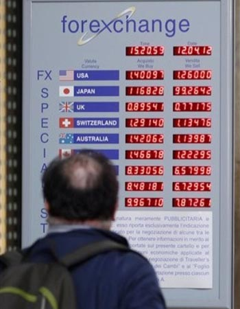 A man checks prices on a foreign exchange currency screen, in downtown Milan, Italy. — AP Photo