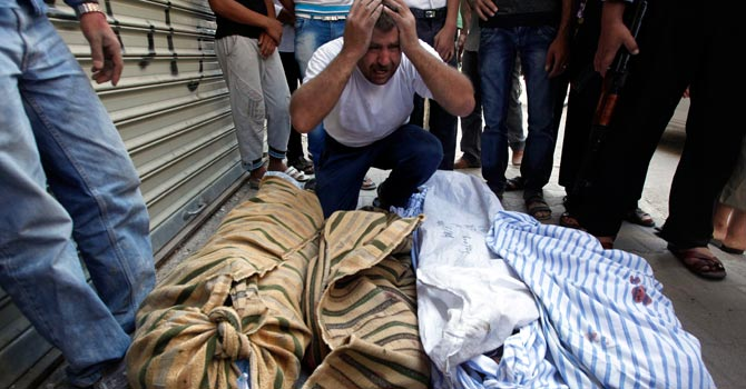 A Syrian man grieves over the bodies of four members of his family. — AP Photo
