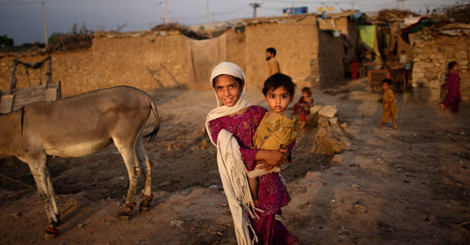 Afghan refugee Nazo Khyber, 8, holds her brother Bilal, 1, while walking back to her home in a slum area on the outskirts of Islamabad, Pakistan, Friday, July 20, 2012. -AP Photo