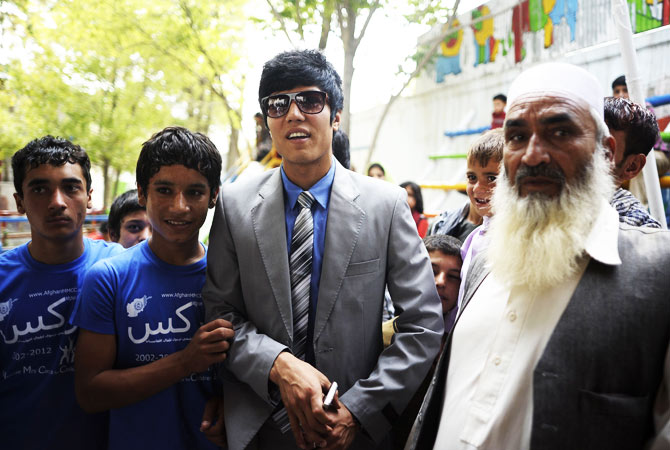 Afghan Olympian bronze winner, in taekwondo, Rohulla Nikpai (C) poses for a picture as he arrives for the Championships.