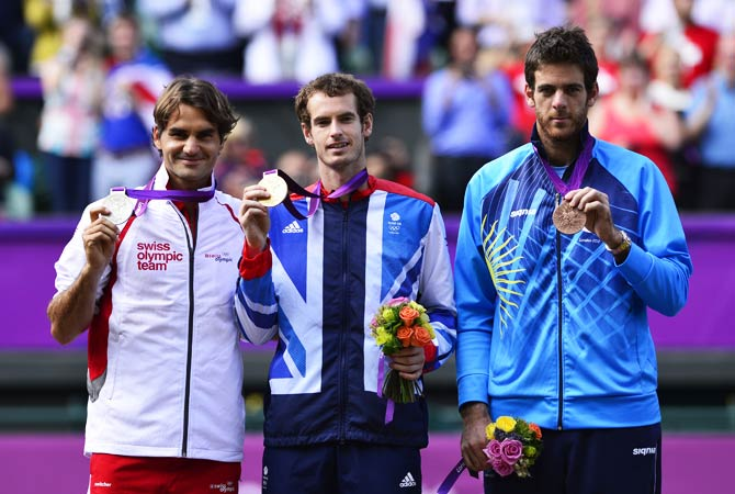 Great Britain's Andy Murray (C), Switzerland's Roger Federer (L) and Argentina's Juan Martin del Potro pose on the podium with their gold, silver and bronze medals respectively, at the end of the men's singles tennis tournament. - Photo by AFP