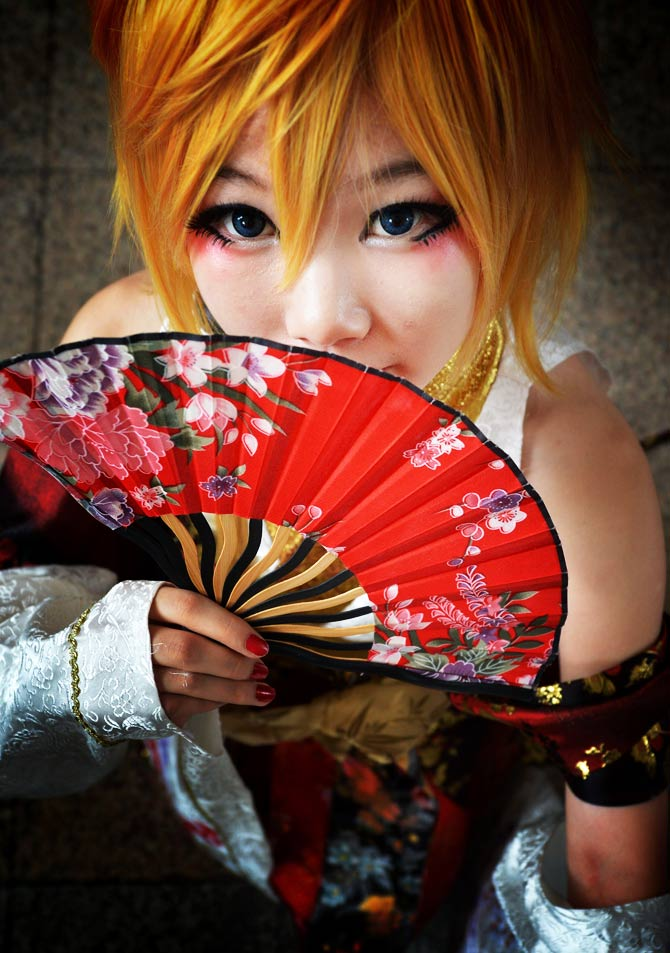 A cosplayer peeks from her crimson fan. - Photo by AFP