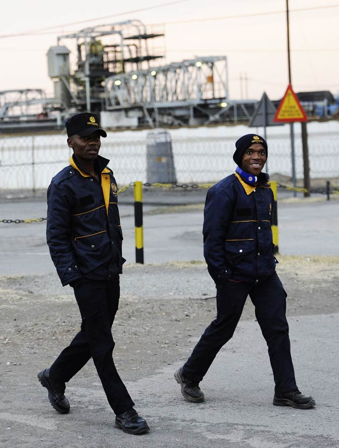 Two guards walk outside the Lonmin platinum mine in Marikana. – Photo by AFP