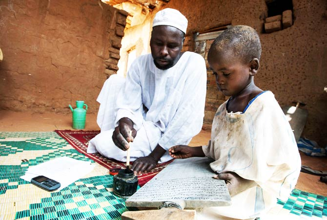 Ahmed Ibrahim Ahmed teaches his son Adam how to write on the wooden boards. ? Photo by AFP