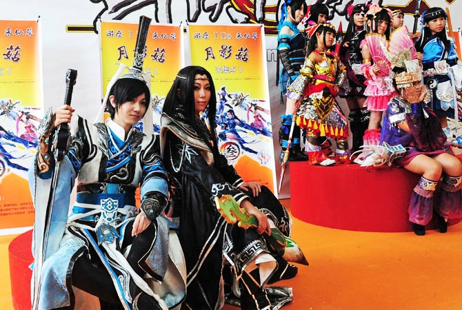 Two groups of cosplayers pose for their photos. - Photo by AFP