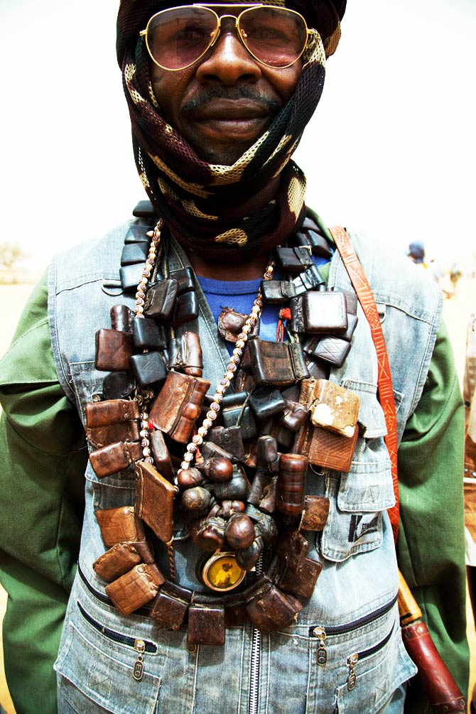"A member of the rebel movement Sudan Liberation Army wears several ""hijabs"" attached to his gun machine for protection against the enemy. ? Photo by AFP"