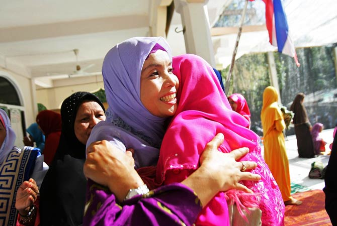 Thai Muslim women embrace after offering prayers at a mosque in Thailand's southern province of Narathiwat. - Photo by AFP