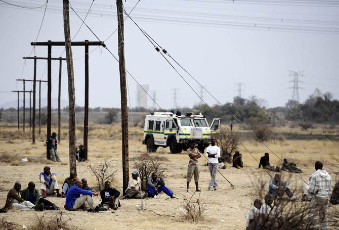 Miners gather in protest as a police vehicle surveys them from afar. – Photo by AFP