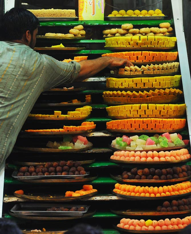 A Pakistani man arranges sweets at his shop ahead of the Muslim festivities. - Photo by AFP