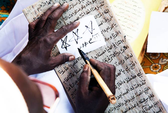 Sidig Ahmad Mohamed draws some religious symbols during the preparation of the treatment. ? Photo by AFP