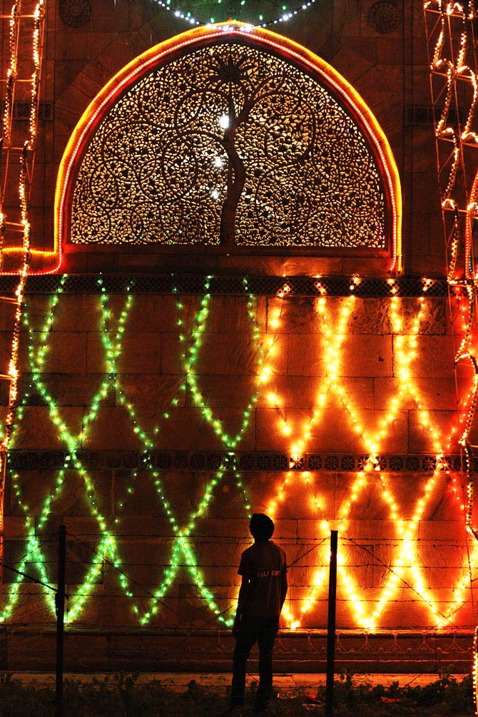 An electrical technician inspects decorative lights on the illuminated Sidi Saiyad Jali Mosque during the holy month Muslim of Ramadan. - Photo by AFP