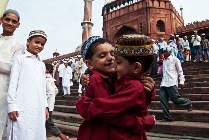 Young Indian Muslims embrace after offering Eid al-Fitr prayers at the Jama Masjid Mosque in New Delhi. - Photo by AFP