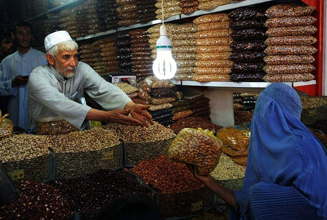 An Afghan woman buys dry fruits during the month of Ramadan as Eid al-Fitr approaches in Herat. - Photo by AFP