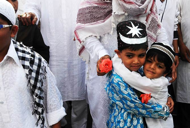 Indian Muslim children greet each other after offering Eid al-Fitr prayers on a street outside the railway station in Mumbai. - Photo by AFP