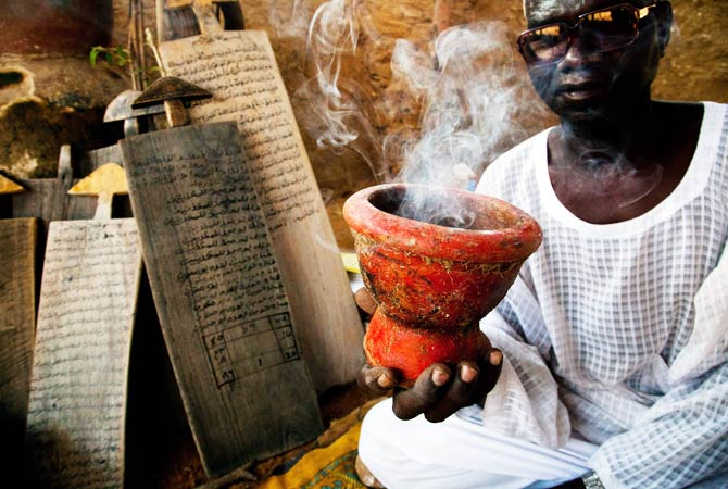 "Sidig Ahmad Mohamed holds a smoking pot during the preparation of the ""Bakhra.? ? Photo by AFP"