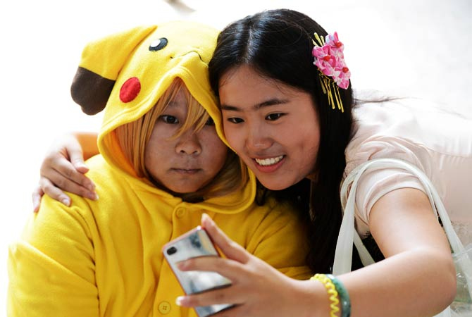 A cosplayer dressed as Pikachu poses with her friend for a picture. - Photo by AFP