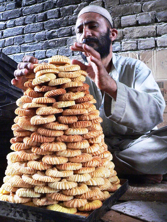 An Afghan baker arranges traditional cookies as Eid-e Fitr approaches, during the month of Ramadan in Jalalabad. - Photo by AFP