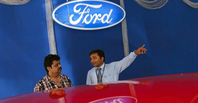 An employee speaks to a potential customer next to a Ford car inside the company's showroom in Mumbai.—Reuters Photo