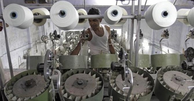 An Indian man works at a textile factory in Ahmadabad. — AP Photo