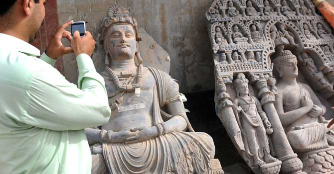 A visitor takes photographs on his mobile of seized ancient statues at a museum in Karachi.  – Photo by AFP