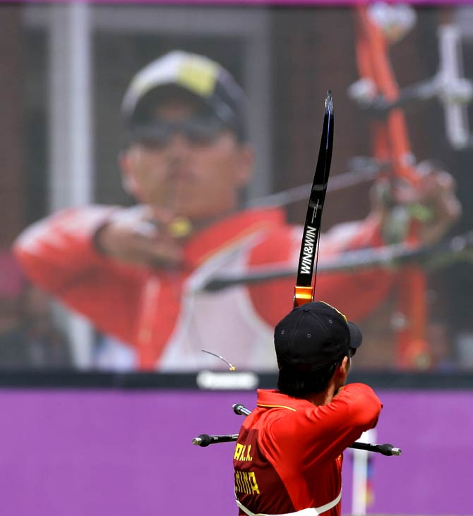 China's Dai Xiaoxiang shoots for a silver medal during the men's individual archery competition. - Photo by AP