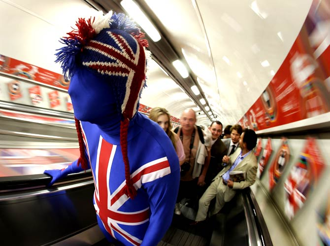 A man dressed in support of  Britain rides an escalator from the tube at Hyde Park. - Photo by AP