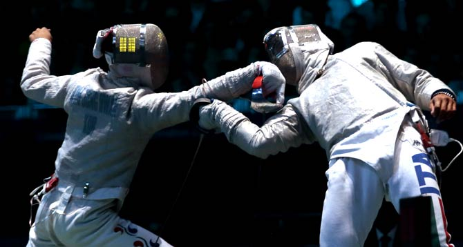 Kim Junghwan of South Korea, left, and Diego Occhiuzzi of Italy, compete during their  men's team saber fencing semifinal match- Photo by AP