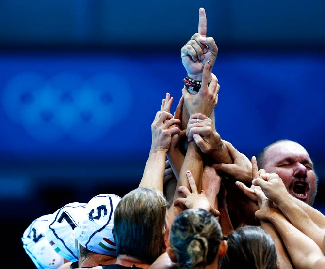 Hungary's coach Andras Meresz, top right, shouts as his team gathers around his arm after beating Russia 11-10 during their women's water polo quarterfinal match. -Photo by AP