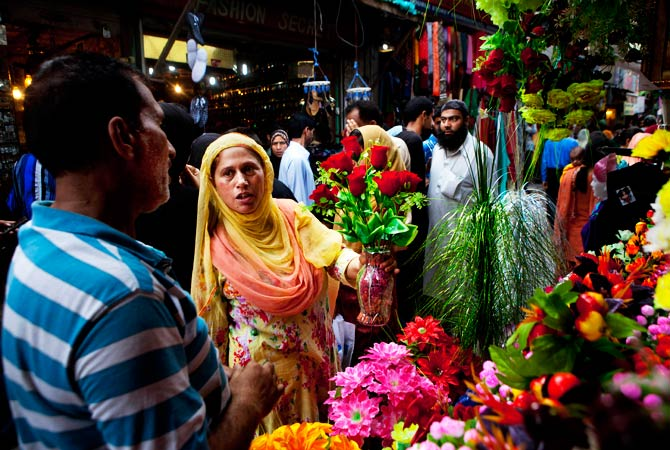 A Kashmiri Muslim woman buys artificial flowers as she shops ahead of Eid. - Photo by AP