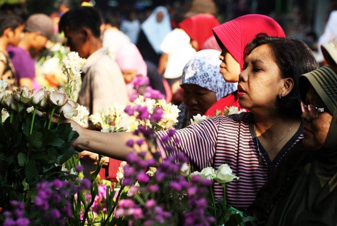 Indonesian women buy flowers  in preparation for Eid al-Fitr holiday at a market in Jakarta. - Photo by AP