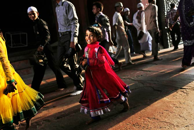An Indian Muslim girl smiles as she arrives in a fancy dress for Eid prayers. - Photo by AP