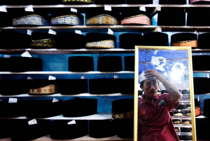 A Muslim man is reflected in a mirror as he tries on a songkok cap at a Ramadan bazaar in Klang, outside Kuala Lumpur. - Photo by AP