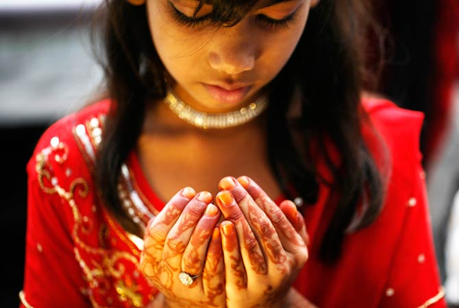 A Nepalese girl offers Eid prayers at a mosque in Katmandu - Photo by AP